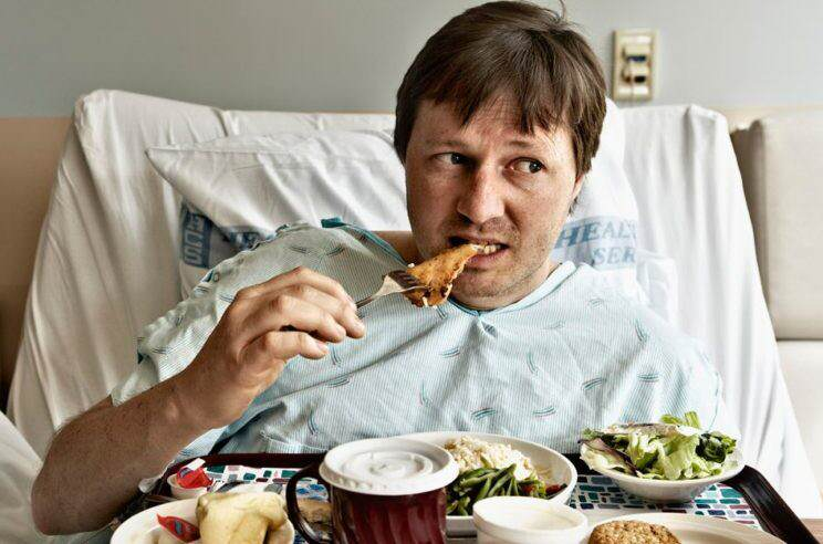 Man-in-hospital-bed-eating-chicken-from-tray-of-food